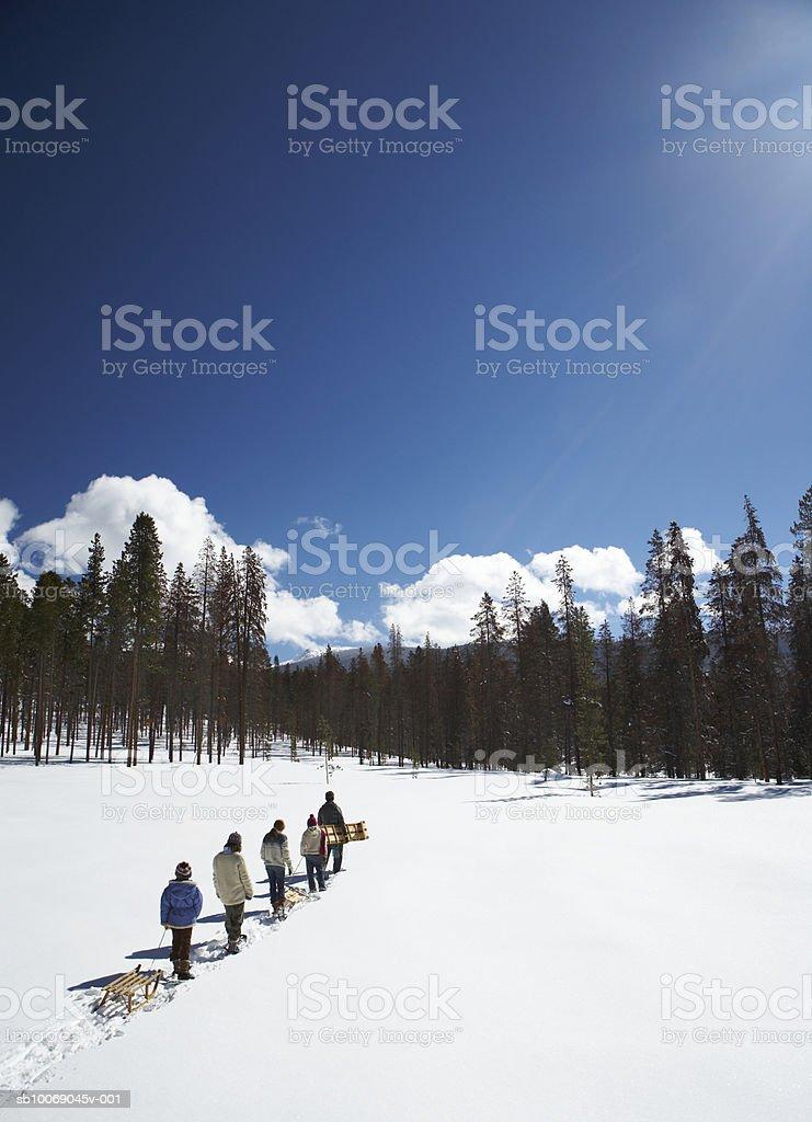 Los padres con niños (8-13) con sled caminar en la nieve foto de stock libre de derechos