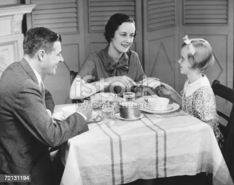 57520540 istock photo Parents with daughter (8-9) eating breakfast at home (B&W) 72131194