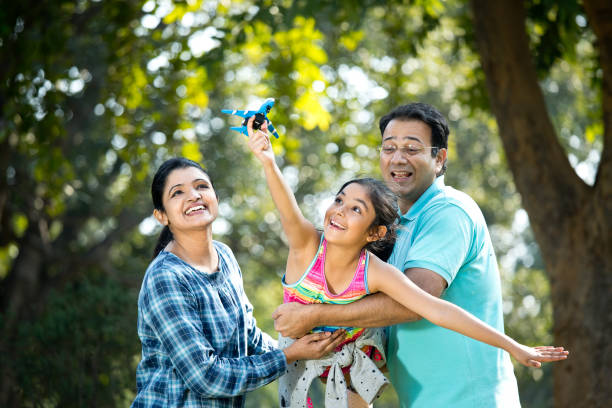 Parents with daughter flying toy airplane Parents lifting daughter helping her fly toy model airplane indian family stock pictures, royalty-free photos & images