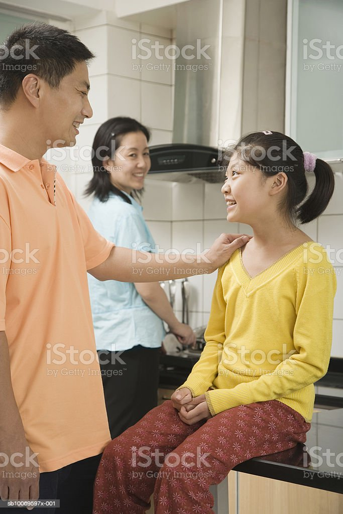 Parents with daughter (10-11) in kitchen, father talking to daughter royalty-free stock photo