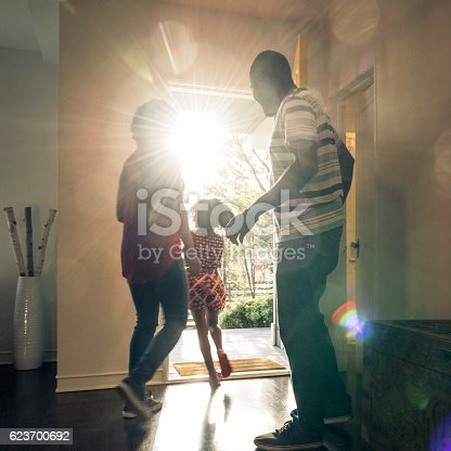 The young girl is running through the open front door and the mother and father are getting ready to leave