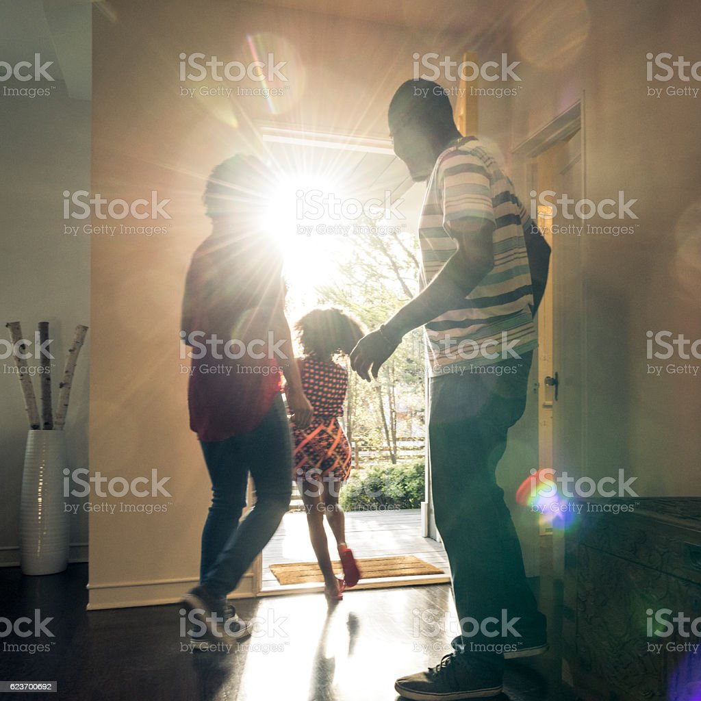 Parents with daughter leaving  the house in bright sunlight stock photo