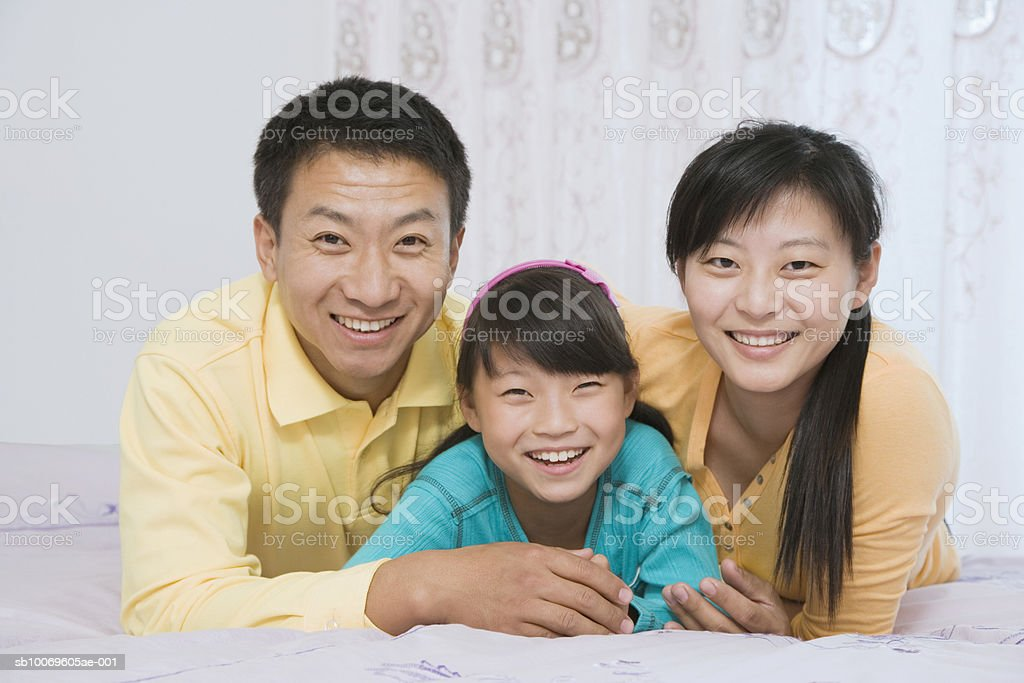 Parents with daughter (8-9)  lying on bed, smiling, portrait Lizenzfreies stock-foto