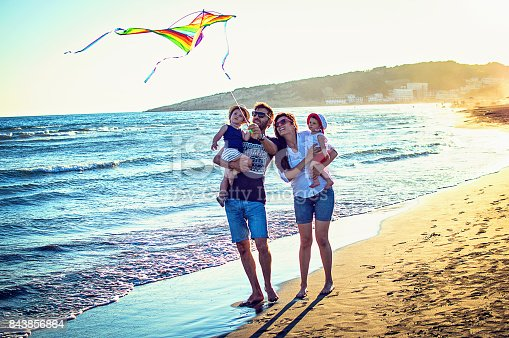 istock Parents with daughters flying kite together at tropical sunny beach 843856864