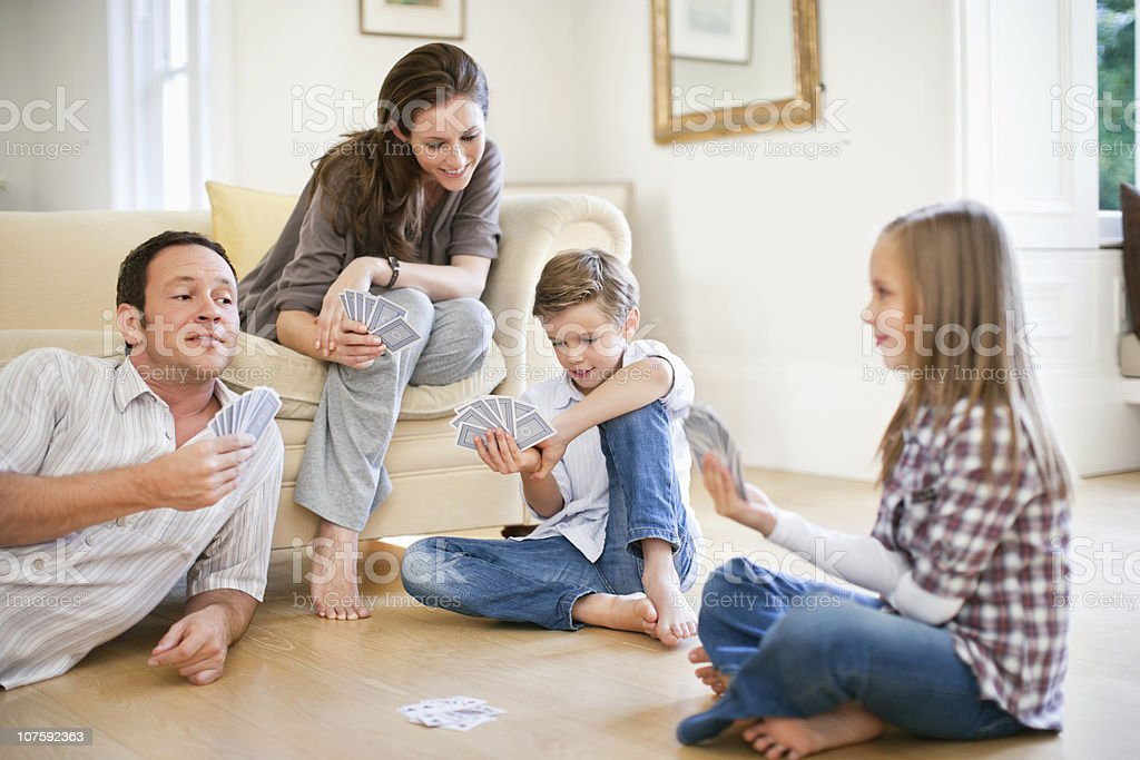 Parents with kids (8-11) playing cards in living room stock photo