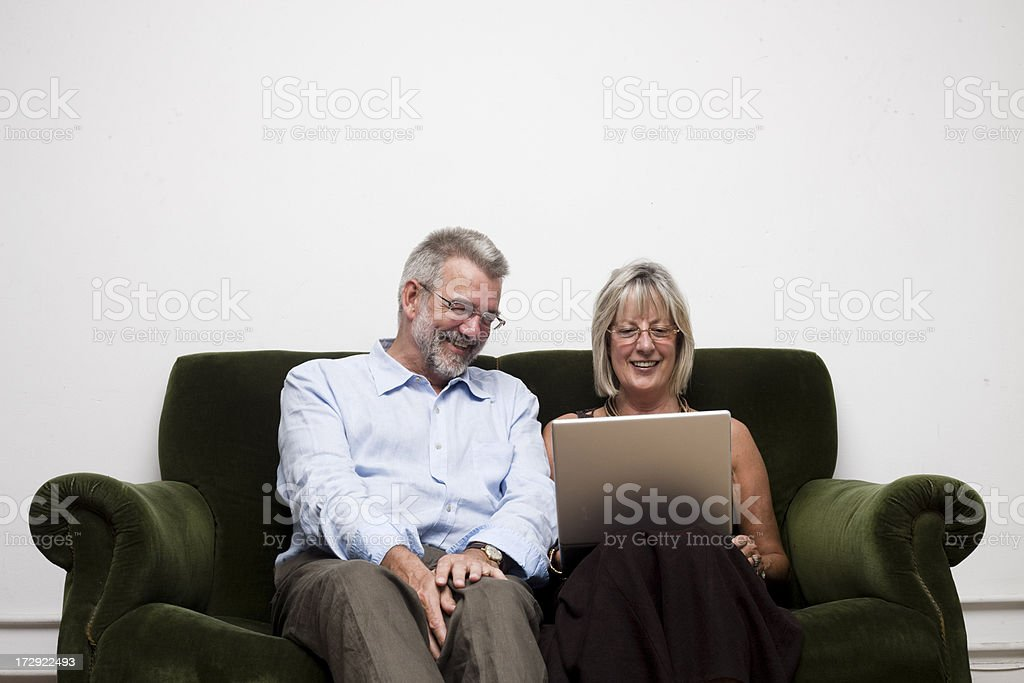 Parents with Laptop Happy mum and dad using laptop on sofa Active Seniors Stock Photo