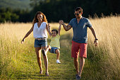 parents with playful little laughing son outdoors in summer grassland