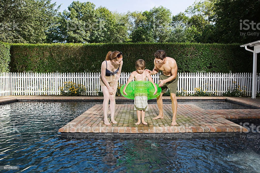 Parents with scared son around swimming pool royalty-free stock photo