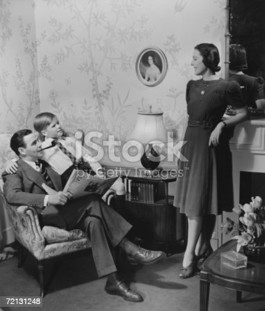 57520540 istock photo Parents with son (8-9) in living room (B&W) 72131248