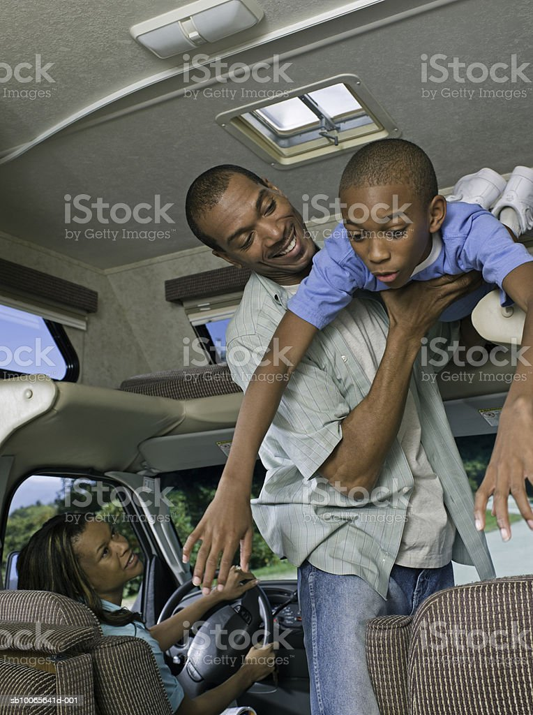 Parents with son (12-13) in motorhome, father lifting son foto de stock libre de derechos