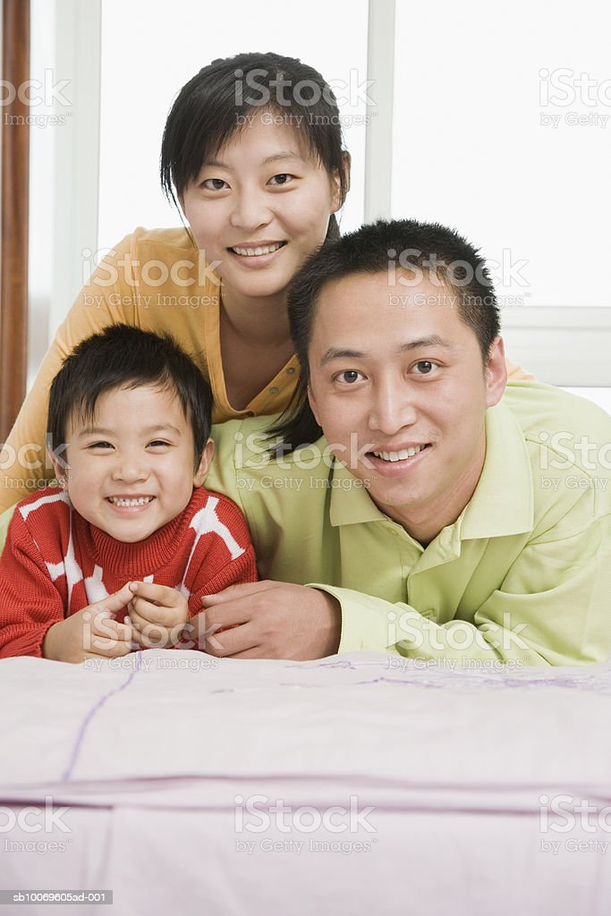 Parents with son (4-5) lying on bed, smiling, portrait royalty free stockfoto
