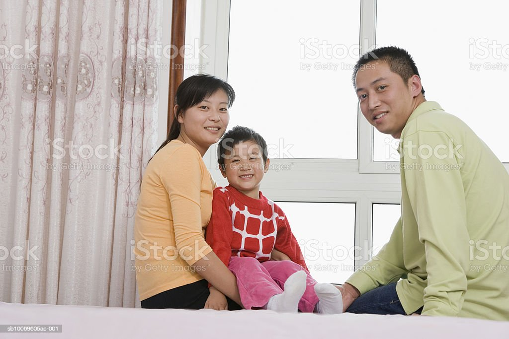 Parents with son (4-5) sitting on bed, smiling, portrait foto royalty-free