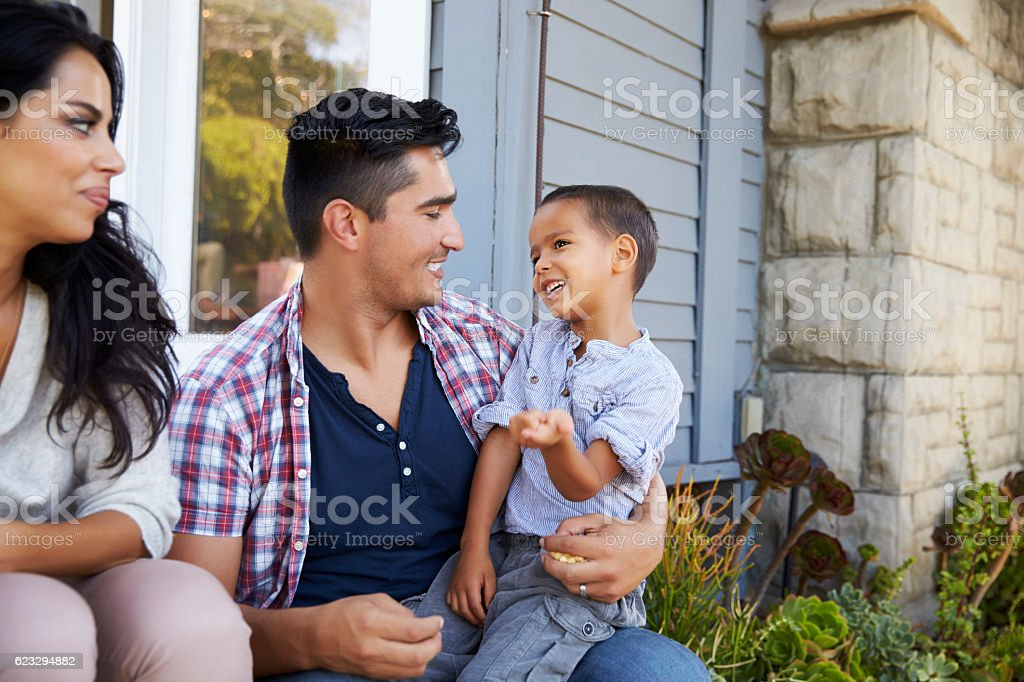 Parents With Son Sitting On Steps Outside Home royalty-free stock photo