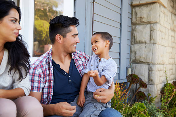 Parents With Son Sitting On Steps Outside Home stock photo