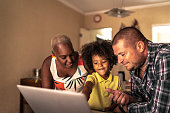 Parents with son using laptop at home