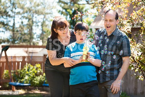 istock Parents with their autistic and down syndrome child in daily lives 986767564