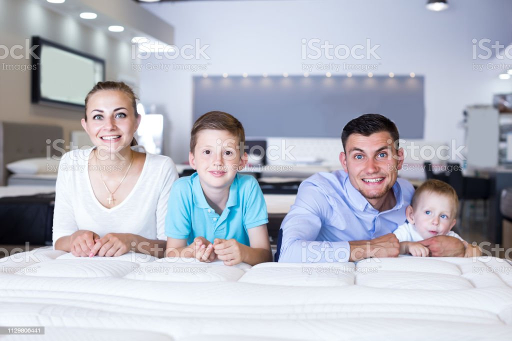happy russian parents with two young sons testing mattress in store