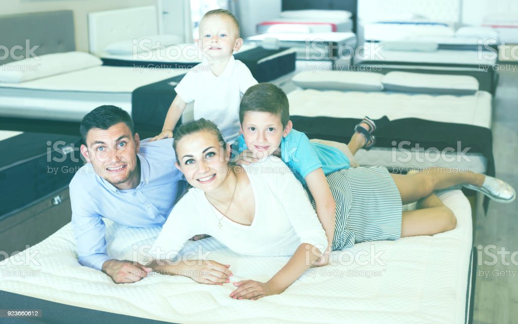 Smiling germany parents with two young sons testing mattress in store