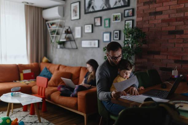 Eltern arbeiten von zu Hause aus, während ihr Kind im Wohnzimmer spielt – Foto