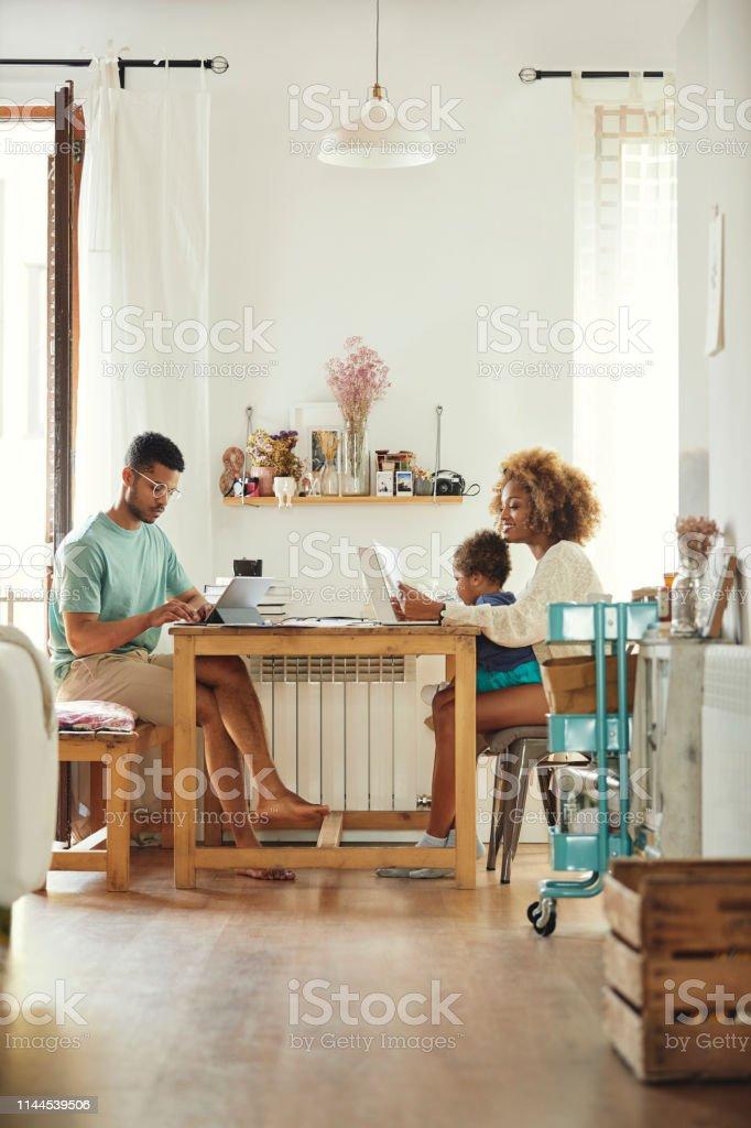 Eltern arbeiten im Sitzen mit Sohn zu Hause - Lizenzfrei 2-3 Jahre Stock-Foto