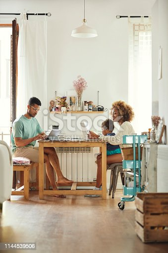 Man using digital tablet while working from home. Woman using laptop with son at table. They are sitting in kitchen.