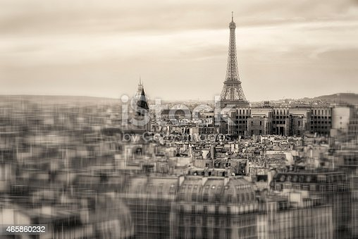 Aerial view of Paris and of the Eiffel Tower from above. Very traditional image in black and white showing the skyline of Paris and the old rooftops, along the landmarks well known to tourists. The selective focus and blur add interest
