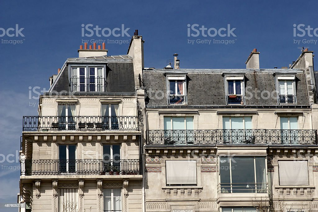 Paris apartment building facade, chimneys, rooftop and balconies, French architecture stock photo
