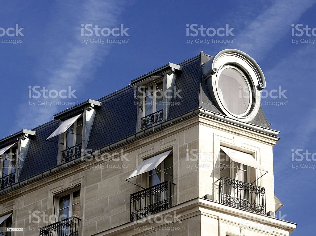 Paris apartment building facade with rooftop, windows and shades stock photo
