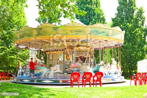 Paris, France - May 20, 2009. Carousel in motion at the Parc de Bercy close to the river Seine. Two woman on the left look out for their children.