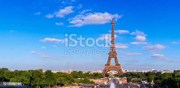 The Eiffel Tower in Paris under a nicely partly clouded blue sky