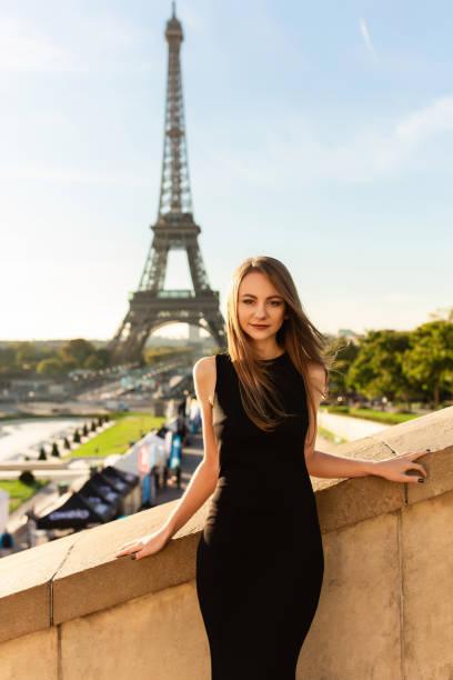 paris mode. frau im schwarzen kleid posiert in der nähe des eiffelturms - hochzeitsreise 1 woche stock-fotos und bilder