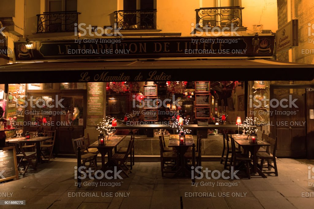 Paris, France, 10.12.2016 - tables, chairs and front entrance of Le Marmiton De Lutece Restaurance at night in Paris, France stock photo