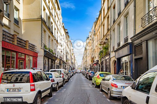 Paris France Rue de Poitou street scene on a sunny day with cars parked on each side of the narrow street in front of shops and art galleries.