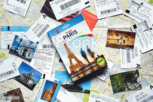 Celje, Slovenia - May 12, 2016: Loney Planet guidebook with map of Paris and various tickets from Paris tourist attractions on it. Real tickets for Sacre Cour, Pantheon, Eiffel Tower, Arc de Triomphe and different museums. Overhead view.