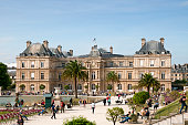 Paris : Jardin du Luxembourg with Senate in background. People walking or having a break in foreground . Paris in France. April 18, 2019
