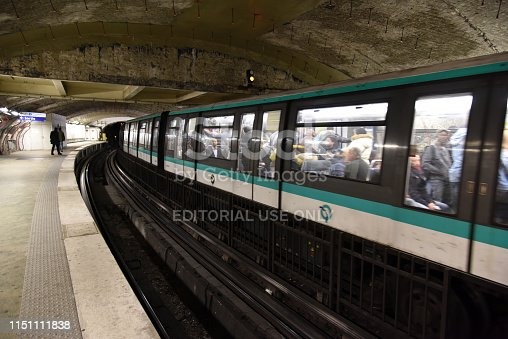 A train composition of Paris Métro waiting at a platform. The Paris Métro was opened in 1900 and has now a system length of 214 km.