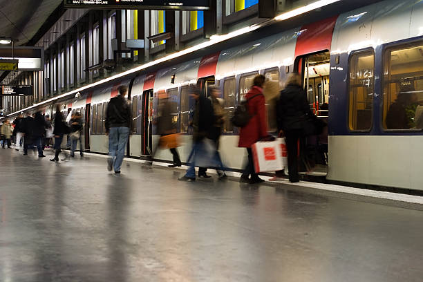Paris Metro Stop Busy weekend commuters board an RER train. The Paris RER trains link to the city's metro network. Note that two advertisements and one woman's face have been removed. Long shutter speed implies motion and activity. subway platform stock pictures, royalty-free photos & images