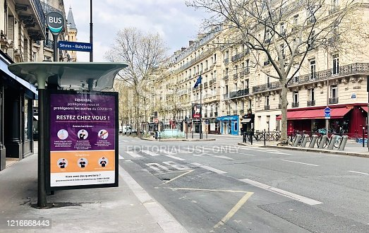 Boulevard Raspail is empty during pandemic Covid 19 in Europe. There are no people and no cars because people must stay at home and be confine. Schools, restaurants, stores, museums... are closed. On the bus shelter, posters to remind people to stay at home.  Paris, in France. April 3, 2020.