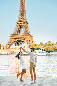 Shot of a happy young couple dancing at the water's edge in the city of Paris