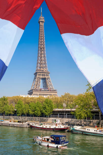Paris with Eiffel Tower against french flag during spring time in France stock photo