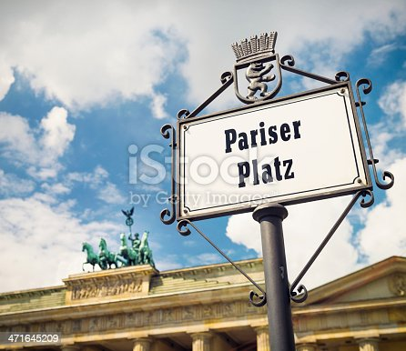 A sign for Pariser Platz in front of the iconic quadriga statue on top of the Brandenburg Gate in central Berlin.