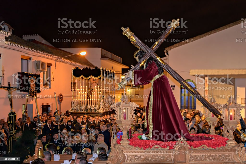Parishioners carry religious floats during Holy Week Easter night procession in Churriana, Malaga. stock photo