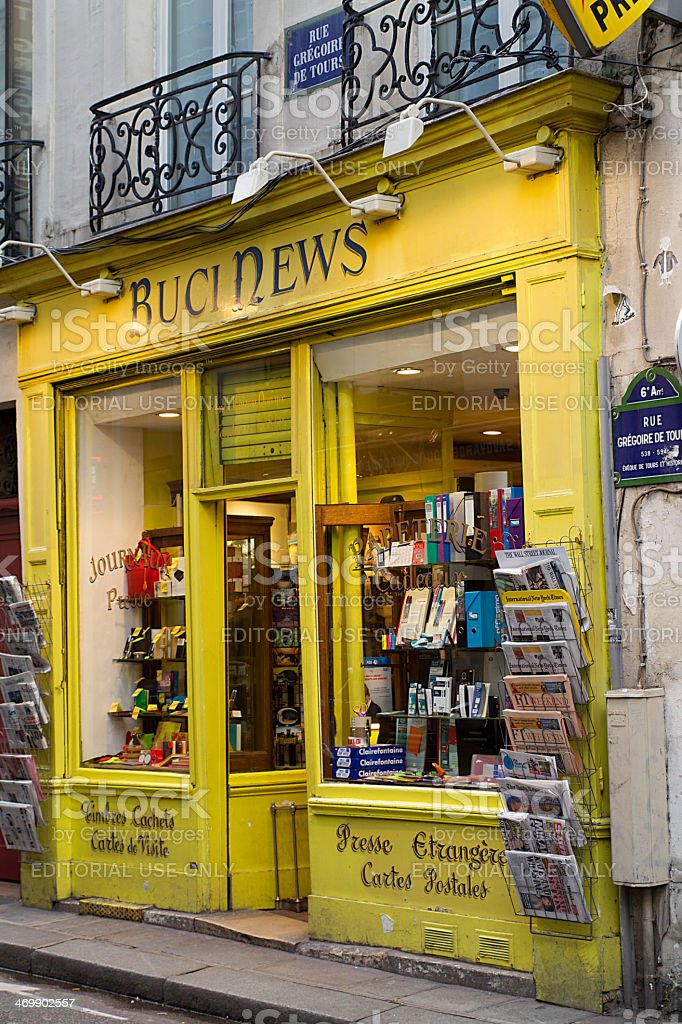 Parisian bookshop stationery Paris, France - January 18, 2014: Typical facade of an old bookshop Parisian stationery situated in the famous Latin Quarter, Rue Grégoire de Tours. On the facade are doors-magazines (-reviews) with newspapers and daily press. Book Cover Stock Photo