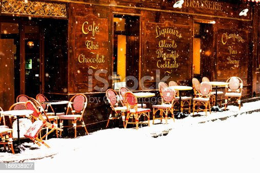 Wooden parisian coffee house with it's sidewalk tables and chairs in winter with the snow falling