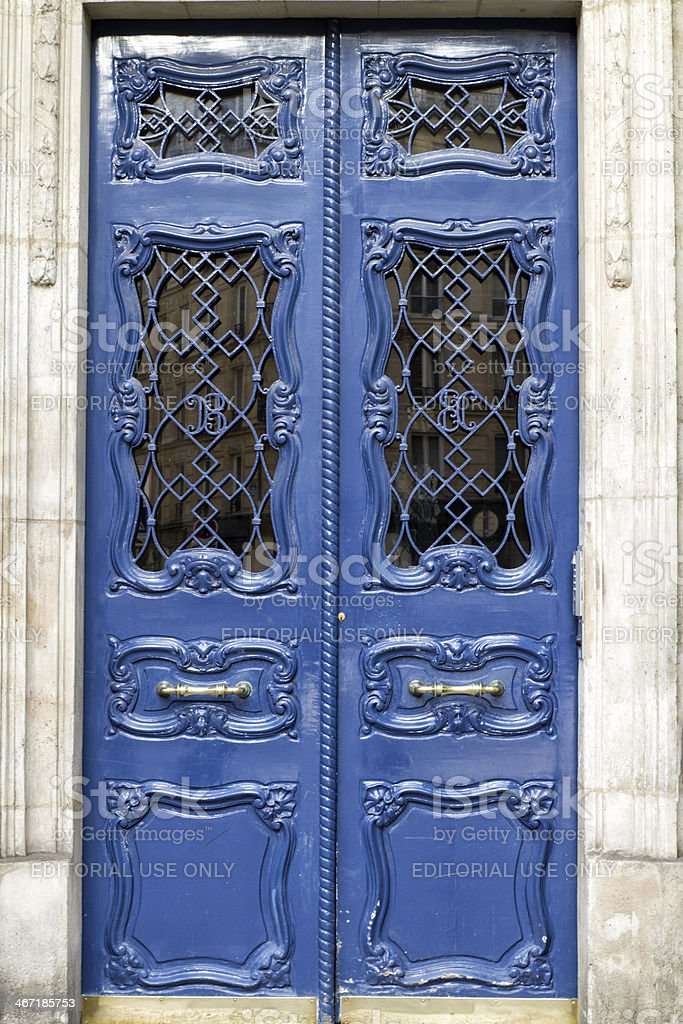 """Parisian front door with reflections building in the window Paris, France, January 18, 2014: Door of outside of typically Parisian blue color. It is situated in the """"Latin Quarter"""" in Paris, more exactly Boulevard Saint-Germain. The facade of a building of Haussmann type is reflected in the window. Abstract Stock Photo"""