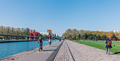 People walking, running and riding bikes on riverside  of Park de la villette in Paris, France
