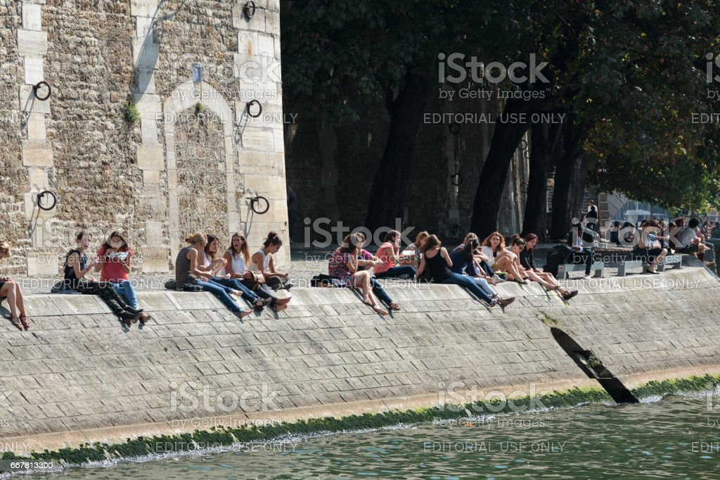 Parisians and tourists have picnic and relax on St Louis island. Seine embankment is popular spot for picnic and promenades at weekends. Paris, France stock photo