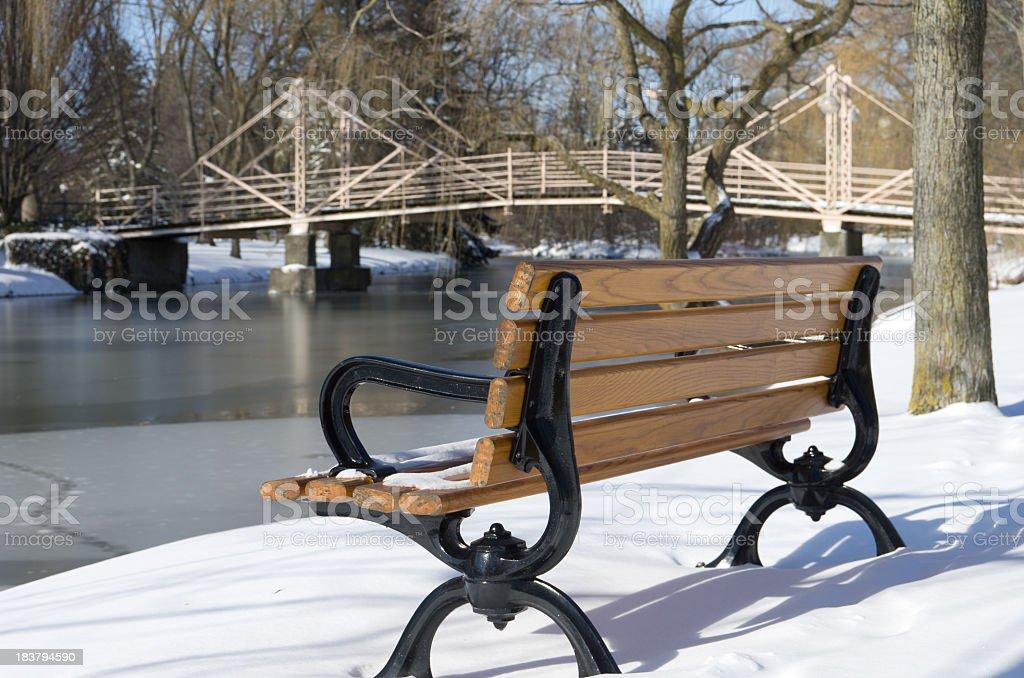 Park Bench by Bridge in Winter stock photo