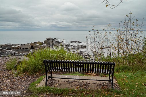 876420064istockphoto Park bench facing rocky shore of Lake Superior in Northern Minnesota on a cloudy day 1059031752