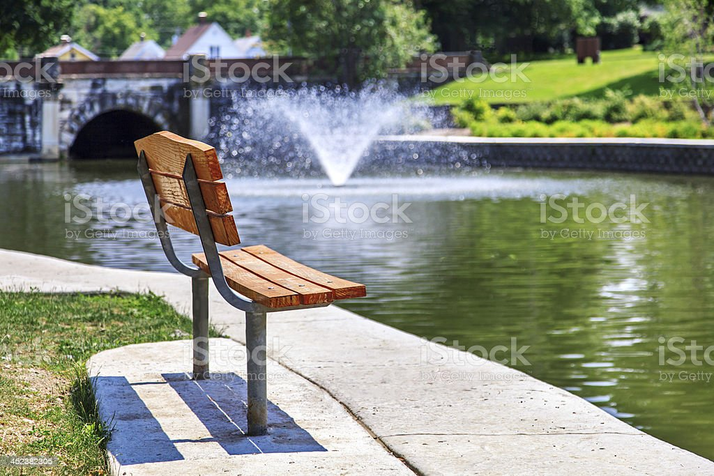 Park bench overlooking pond stock photo